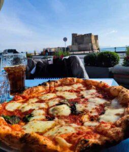 Estate a Napoli la pizza sul lungomare con vista sul castel dell'ovo